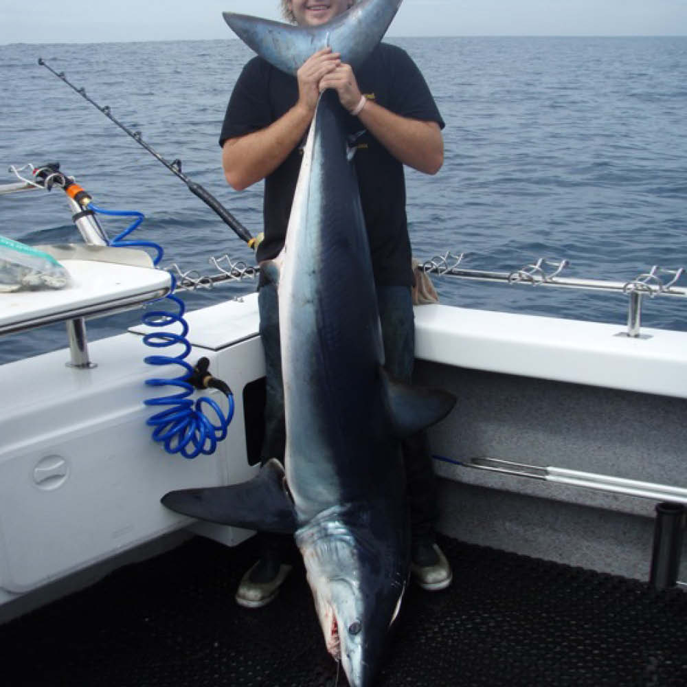 man holding gummy shark bag out fishing charters